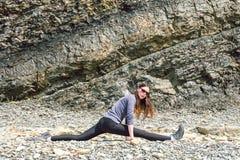 行使一个健康成熟妇女的形象的侧视图舒展和在岩石平台 库存照片