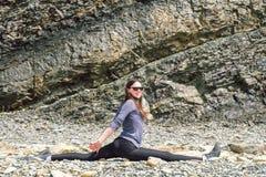 行使一个健康成熟妇女的形象的侧视图舒展和在岩石平台 库存图片
