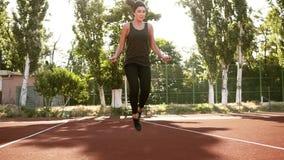 行使与一条跳绳的运动的brinette女孩,跳高,移动绳索几次 户外体育场 影视素材