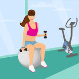行使与两哑铃重量的美丽的妇女坐健身球 免版税库存照片