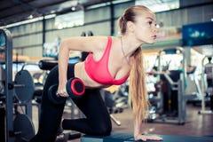 行使与哑铃的可爱的坚强的妇女在健身房 免版税库存照片