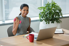 行使与哑铃的微笑的执行委员,当工作膝上型计算机时 免版税库存照片