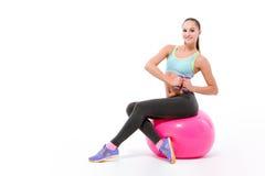 行使与哑铃的年轻女运动员坐fitball 免版税图库摄影
