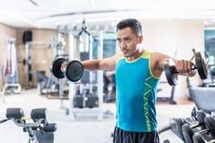 行使与在一家现代健身俱乐部的哑铃的英俊的坚定的年轻人 免版税库存图片