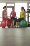 行使与在健身房的健身球的三名微笑的成熟妇女 库存图片