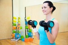 行使与在健身房的哑铃的愉快的运动的妇女 免版税库存图片