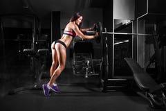 行使与在健身房的杠铃的健身女孩 免版税图库摄影