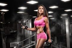 行使与在健身房的杠铃的健身女孩 免版税库存图片