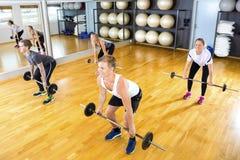 行使与在健身房的杠铃的男性和女性朋友 免版税库存图片