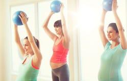 行使与在健身房的球的愉快的孕妇 免版税库存照片