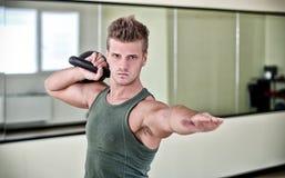 行使与在健身房的kettlebell的英俊的年轻人 库存图片