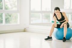 行使与在健身球的哑铃的性感的亚裔女孩在与拷贝空间、体育和健康生活方式的健身健身房 免版税库存照片
