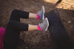 行使与巨大的轮胎的妇女的低部分在障碍桩期间 库存图片