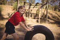 行使与巨大的轮胎的微笑的女孩画象在障碍桩期间 库存图片