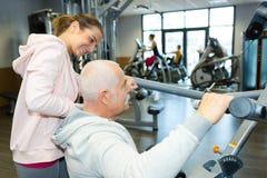 行使与教练员的老人在健身演播室 库存图片