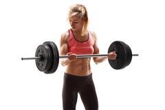行使与杠铃的坚强的肌肉妇女 免版税库存照片