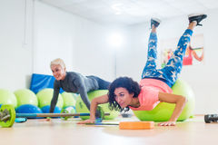 行使与稳定球的两名妇女做在健身房类的俯卧撑 库存图片