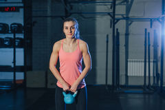 行使与水壶响铃的运动妇女,当在矮小位置时 做crossfit锻炼的肌肉妇女在健身房 库存照片