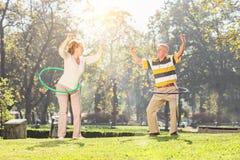行使与hula箍的成熟夫妇在公园 免版税库存照片