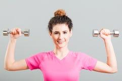 行使为与dumbells的三角肌的年轻微笑的妇女 免版税库存照片