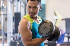 行使二头肌的一个英俊的年轻人的画象卷曲在健身房 免版税库存照片