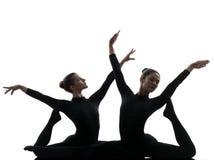 行使体操瑜伽剪影的两名妇女柔术表演者 免版税库存图片