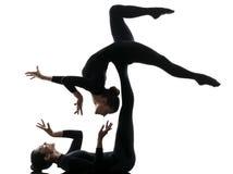 行使体操瑜伽剪影的两名妇女柔术表演者 库存照片