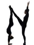 行使体操瑜伽剪影的两名妇女柔术表演者 免版税图库摄影