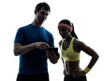 行使健身人教练的妇女使用数字式片剂silhou 图库摄影