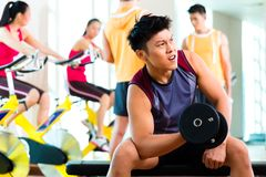 行使健身的亚裔人民体育在健身房 免版税图库摄影