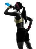 行使健身饮用的能量饮料剪影的妇女 免版税图库摄影