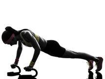 行使健身锻炼俯卧撑剪影的妇女 免版税库存图片