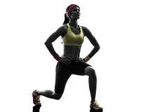 行使健身锻炼刺蹲下的剪影的妇女 免版税库存图片