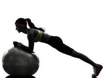 行使健身锻炼板条位置剪影的妇女 免版税库存照片