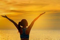 行使剪影健康妇女的生活方式放松和重要在海滩思考和实践的瑜伽在日落 免版税库存照片