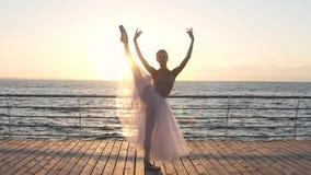 行使华美的白种人的芭蕾舞女演员,舒展户外站立在木地板上在海附近 妇女缠绕 影视素材