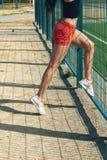 行使在一个晴朗的早晨的美丽的女孩女运动员在体育场 免版税库存照片