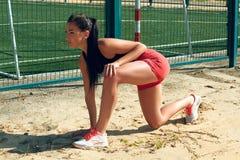 行使在一个晴朗的早晨的美丽的女孩女运动员在体育场 免版税图库摄影