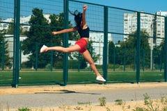 行使在一个晴朗的早晨的美丽的女孩女运动员在体育场 免版税库存图片