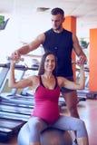 行使在与个人教练员的健身房的微笑的孕妇 图库摄影