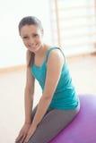 行使在与健身球的健身房的微笑的妇女 库存图片