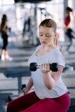 行使在与哑铃的健身健身房的初学者女孩 免版税库存照片