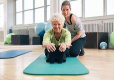 行使在与教练的健身房的资深妇女 免版税库存图片