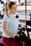 行使在健身俱乐部的初学者胖的女孩 免版税库存图片