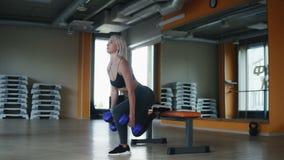 行使在健身俱乐部的嬉戏,白肤金发的妇女做一个腿仰卧起坐,当拿着蓝色时上色了哑铃 侧视图 影视素材