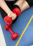 行使在健身席子和举的红色dumbb的妇女特写镜头 库存照片