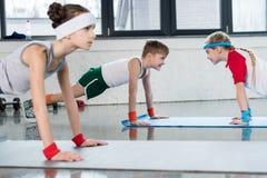 行使在健身房和微笑的瑜伽席子的逗人喜爱的运动的孩子 免版税库存图片
