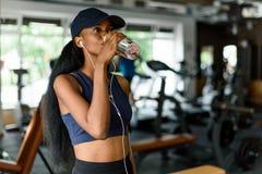 行使在健身房和饮用水的健身妇女从瓶 与肌肉适合亭亭玉立的身体的女性模型 库存图片