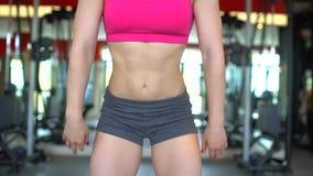 行使在健身房的女运动员仰卧起坐 做蹲坐的肌肉少妇 体育,秀丽,健身的概念 影视素材