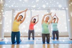 行使在健身房的席子的愉快的孕妇 库存照片
